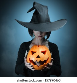 Halloween witch holding a orange pumpkin, which sits inside a mouse