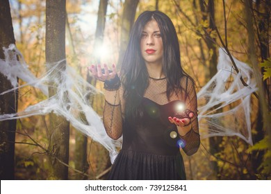 Halloween Witch with magic lights in dark autumn forest. Beautiful young european or american woman in black Gothic dress.Halloween party at city, decor and design for party, mysterious lady in woods