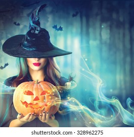 Halloween Witch with a magic Pumpkin in a dark forest. Beautiful young woman in witches hat and costume holding carved pumpkin. Halloween art design