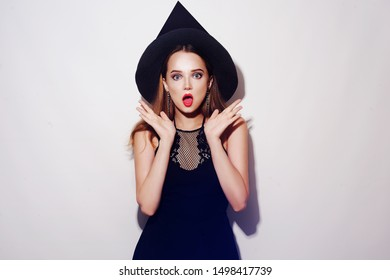 Halloween Witch on white background. Halloween Party girl surprise. Happy Halloween Witch, beautiful young surprised woman in witches hat and dress look in camera