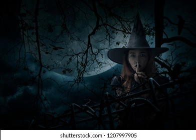 Halloween witch showing silence sign with finger over lips standing over dead tree, crow, birds, full moon and spooky cloudy sky, Halloween mystery concept