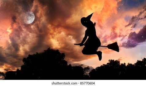 Halloween witch silhouette with glowing eyes flying on broomstick in the evening at dramatic sky with moon and stars