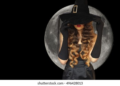 Halloween witch wearing black gloves and moon. Girl in black with red lips and curly hair holding hat. Halloween or New Year concept