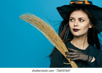 halloween witch woman hat with a broom on a blue background