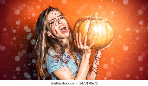 Halloween Woman with bloody make up. Halloween girl in blood with pumpkin. Horror photo of girl murderers hold pumpkin in her hand