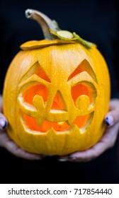 Halloween. Woman hands holding pumpkin on dark