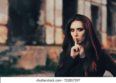 Halloween Woman Keeping a Secret in Front of a Ruins - Hooded woman with finger on the lips in front of a creepy building