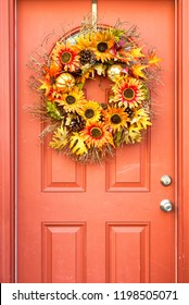 Halloween wreath decoration of fall colors hung on an orange brown door