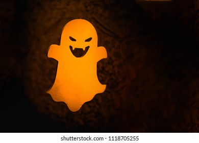 Halloween yellow ghost flying in sky on black background. Dark night. Halloween party. Copy space for text
