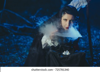 Halloween Young beautiful and mysterious woman witch in woods, in black cloak with hood, witch conjures in the wizard forest