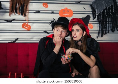 Halloween. young scared caucasian couple in vampires and witch clothing enjoying watching horror movie in television and sitting on sofa in halloween party at home, holiday, halloween festival concept