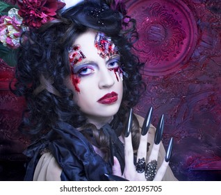 Halloween. Young woman in witch image with bloody makeup ann with skull.
