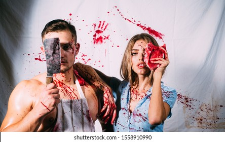 Halloween zombie couple of muscular man and bloody young woman with wounds and red blood. Scary man with blood on face holding a rusty and bloody cleaver and meat in front of his face. Chef killer