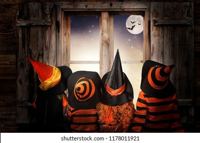 Halloween.Children in costumes of witches and wizard  at night sit near a window andand look at the sky and bats.