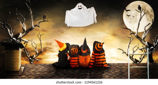 Halloween.Children in costumes of witches and wizard at night sit on the roof look at the flying ghost.