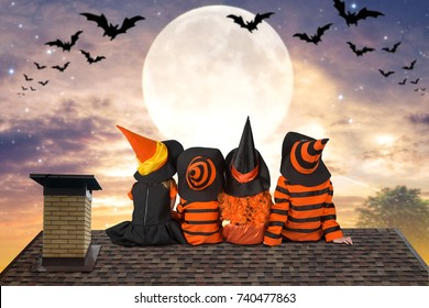 Halloween.Children in costumes of witches and wizard are sitting that night on the roof and look at the sky and bats