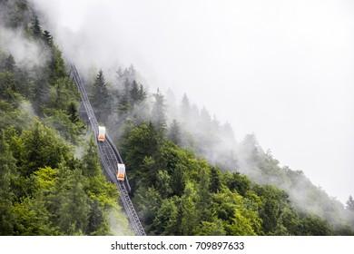 HALLSTATT, AUSTRIA - August 6, 2017: Two wagons crossing on a two-rail funicular in the mountains of Hallstatt, Austria, on a foggy day