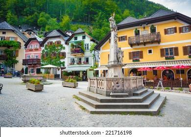 Hallstatt, Austria - August 7, 2013: Religious monument with typyical colorful houses in Hallstatt village, Austria