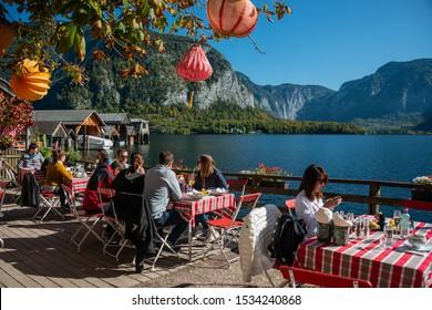 HALLSTATT/ AUSTRIA OCT 12, 2019: Tourist in Restaurant Garden at Hallstatt Lake in the early Morning sun