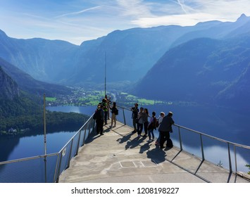 Hallstatt  , Austria - September 11 , 2018 : Tourists taking pictures on Skywalk platform viewing beautiful aerial view scenery of Hallstatt , small village situated on Lake Hallstatt in the morning