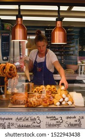 Hallstatt, Austria, September 2019. A girl in a black apron sells traditional Austrian pastries. Delicious crispy cream cake.