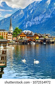 Hallstatt, Austria. View to Hallstattersee Lake and Alps mountains summits. White swan birds near the dock. Ancient houses at lake banks with chapel. Summer day. Blue sky with clouds.