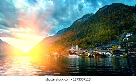 Hallstatt mountain resort village with famous church, traditional alps houses and wooden rural boat houses at Hallstatt lake. Sunrise over austrian alps mountains. Location: Hallstatt, Austria, Alps.
