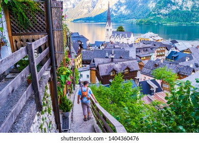 Hallstatt, Salzkammergut, Austria - August 23, 2018: People walking down on narrow old stairs above Hallstatt, with breathtaking views of Lake Hallstatt (Hallstatter See) and the town church.