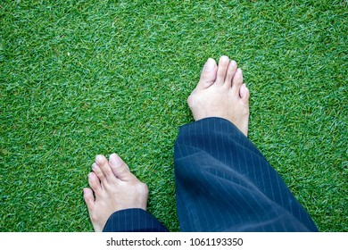 Hallux valgus, woman legs with bunions in trousers stand on green grass backgroud