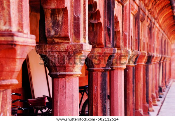 Hallway with columns near the West Gate. Taj Mahal, Agra, India.. Red stone.