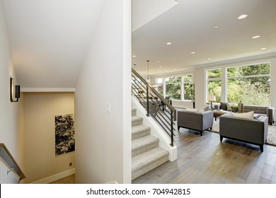 Hallway features white ceiling dotted with pot lighting over modern style family room and a staircase with horizontal hand rails. Northwest, USA