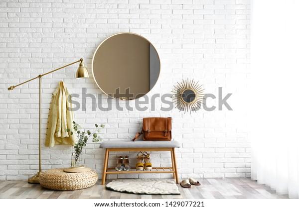 Hallway interior with big round mirror and shoe storage bench near brick wall