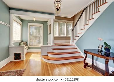 Hallway interior in blue tones, columns and hardwood floor. View of stairs. Northwest, USA