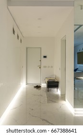 Hallway in a modern style with white walls and a light tiled floor. There is a white door, stand with magazines, shoes on the floor, large mirror on the wall, backlighting. Indoors. Vertical.