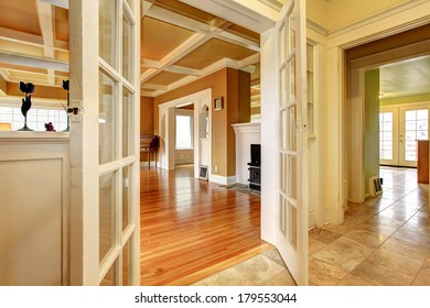 Hallway with an open door to a living room with an antique stove and chest.