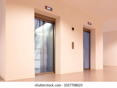 hallway with two elevators and a hall space with a curtain wall in office building
