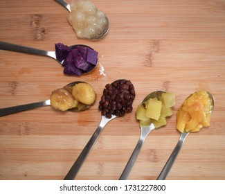 "Halo halo , a Filipino dessert that translates to ""mix mix"". Halo halo ingredients on six spoons with copy space."