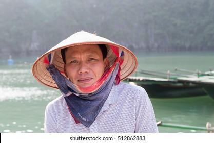 Halong Bay, Vietnam 22 October 2016: Vietnamese fisherman wearing traditional conical hat. Ha Long Bay, Vietnam