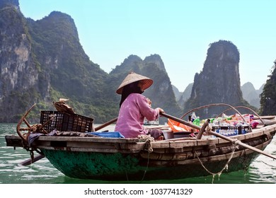 Halong, Vietnam - OCTOBER 30, 2011: A woman is selling food on a boat in the floating village of Kua Wan near the island of Daw Guo in Halong Bay