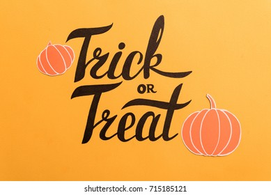 Haloween theme phrase in frame of pumpkins and bats on orange background
