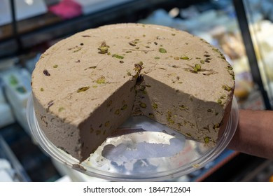 Halva with pistachio on a cutting board isolated on black