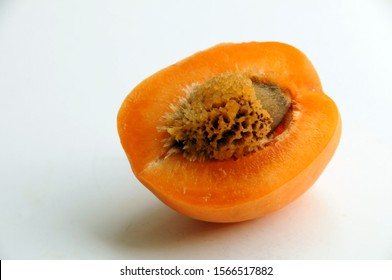 Halved apricot with a stone with interesting remains of the other half
