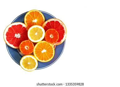 halved citrus fruits on a blue plate, isolated, top view