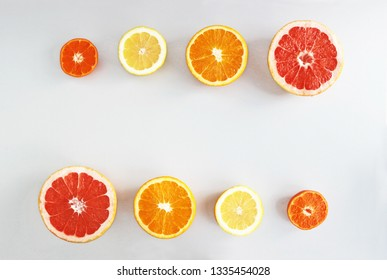 halved citrus fruits  in  a row on gray background, top view