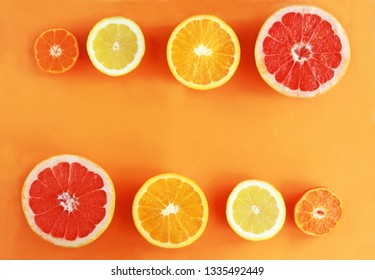halved citrus fruits in a row on orange colored background, top view