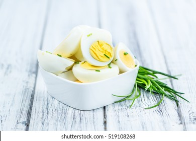 Halved Eggs on wooden background (close-up shot; selective focus)