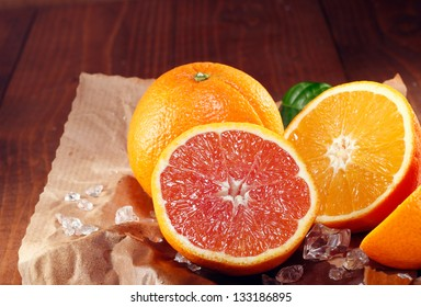 Halved fresh orange varieties with the traditional orange coloured pulp and the cara cara orange with its red-pink colouration on crumpled grungy brown paper