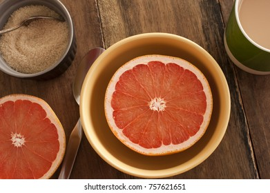 Halved fresh pink or rose grapefruit served in a bowl for breakfast with an accompanying basin of caramelized sugar, overhead view