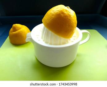 Halved lemon is juiced on a lemon press. Cut out, close up