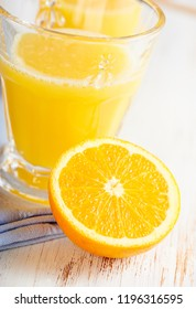 Halved orange and orange juice. Concept for healthy nutrition. White wooden background. Close up.